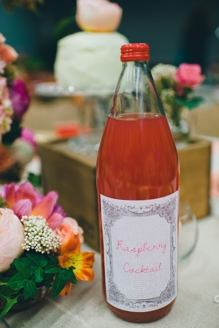 A clear glass bottle filled with pink liquid, with a label printed on fabric stating raspberry cocktail.