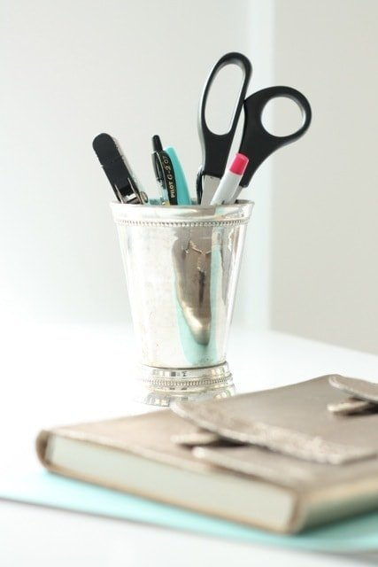 A vase filled with pens, sharpies, and scissors.