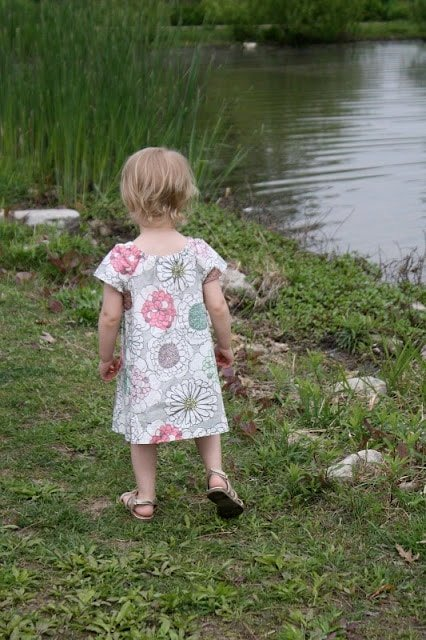 A little girl walking in the grass next to water.