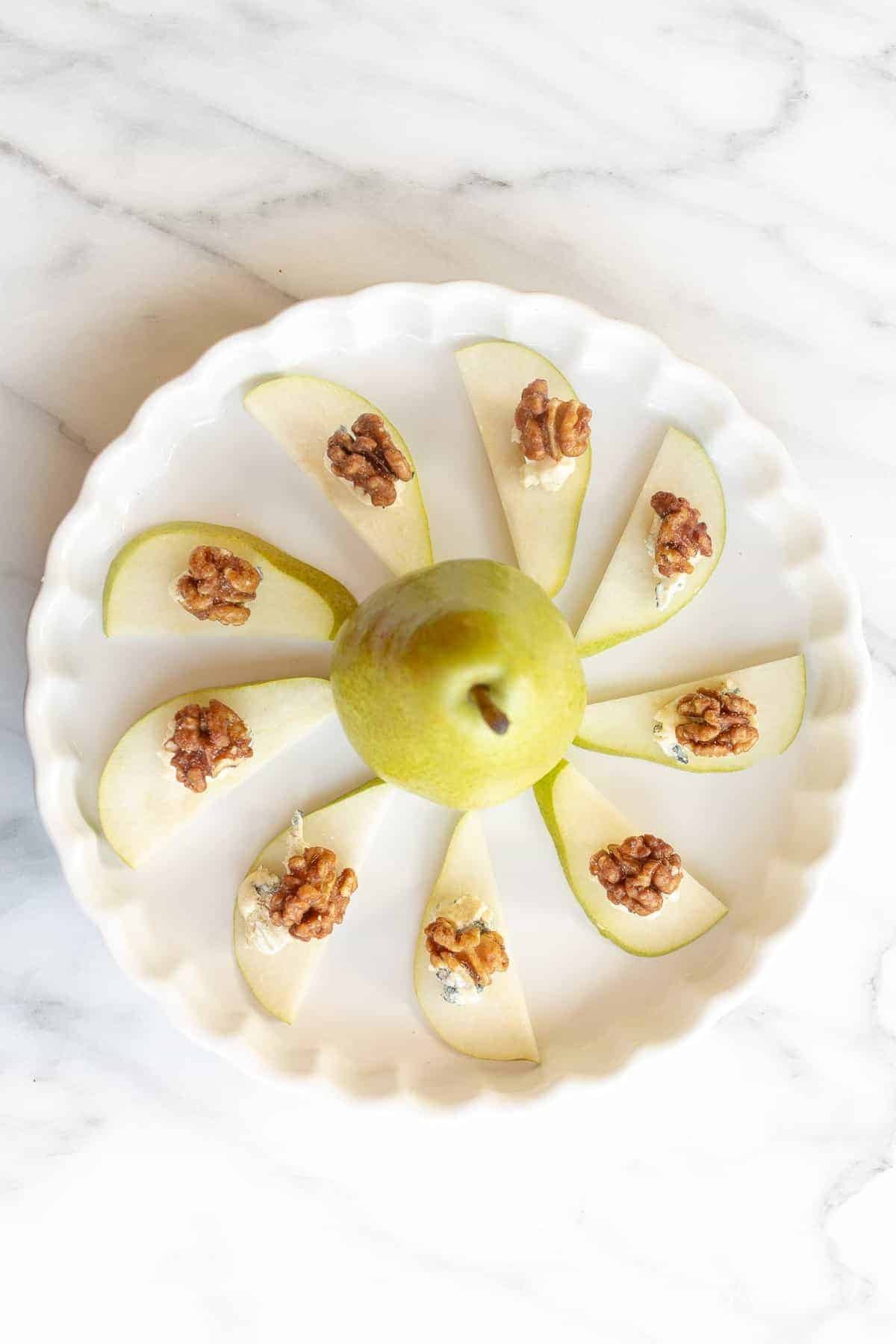 a healthy appetizer of pears with blue cheese and walnuts on a platter