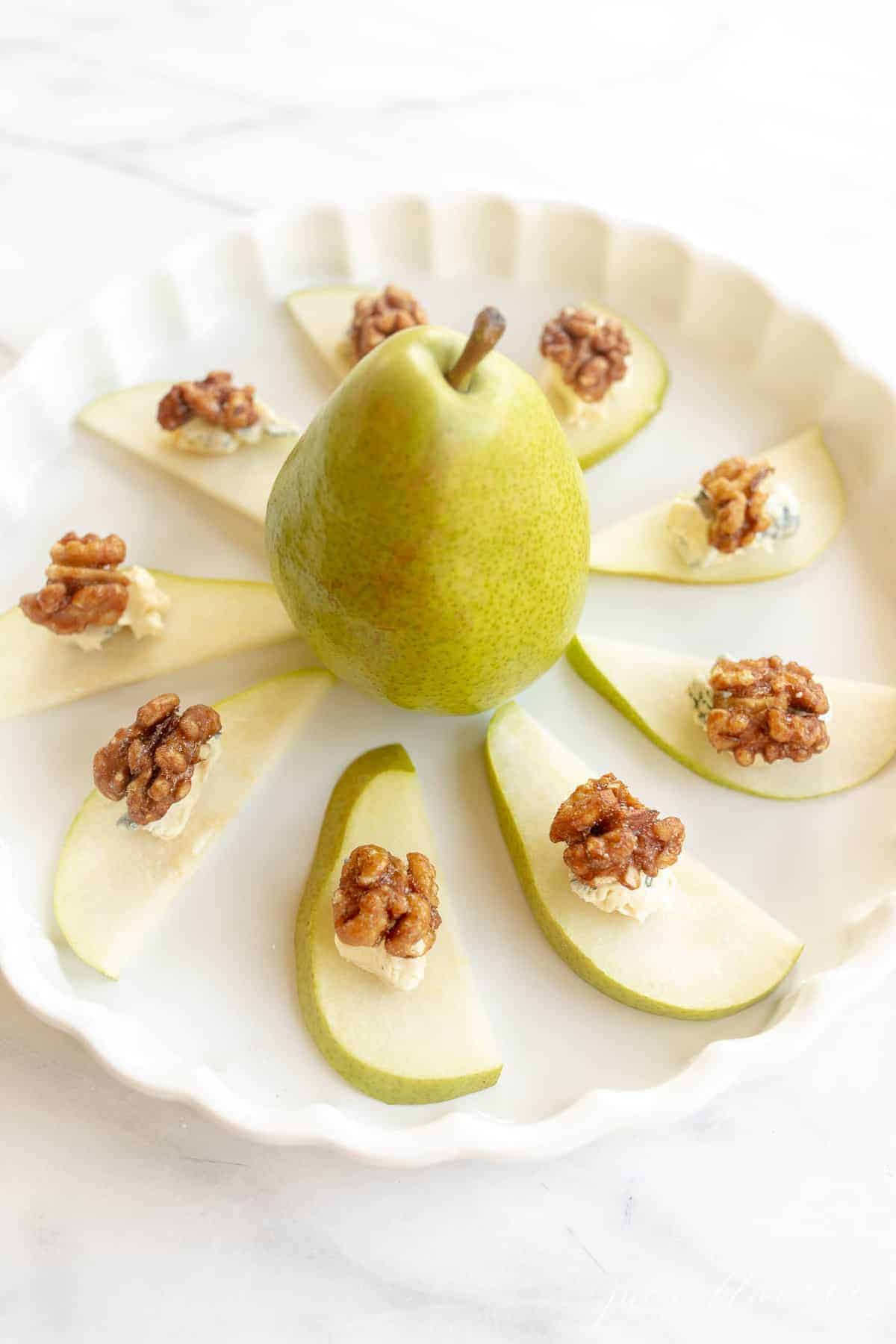 pear appetizer topped with blue cheese and walnuts displayed in a circular white platter