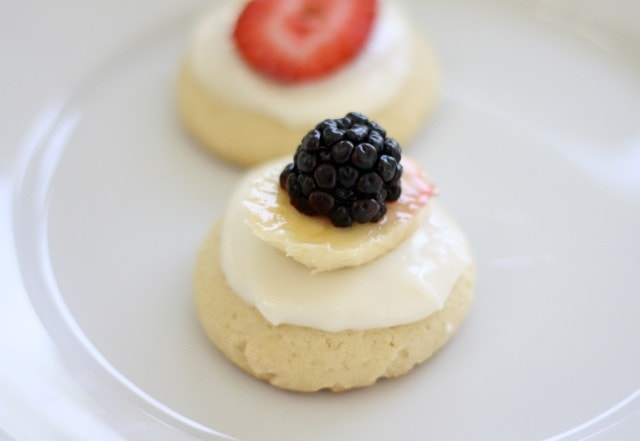 A mini fruit pizza topped with icing and a blackberry