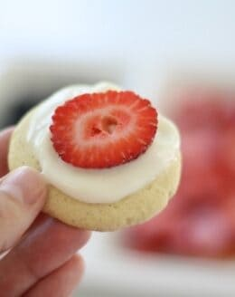 A hand holding a small cookie topped with fruit pizza icing and a sliced strawberry