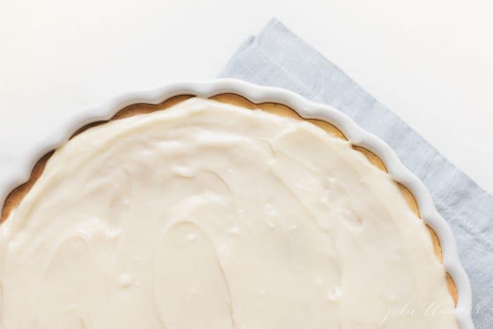 A fruit pizza with fruit pizzing icing in a white dish, blue towel in background.