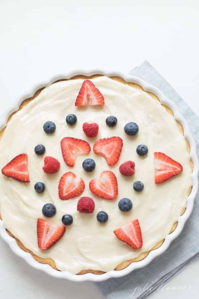 A fruit pizza decorated with fruit pizza icing and sliced berries.
