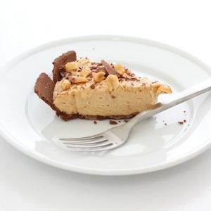 slice of peanut butter and chocolate cheesecake on white plate with fork