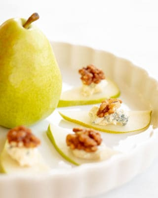 pear slices with blue cheese and candied walnuts on a white platter with pear in the center
