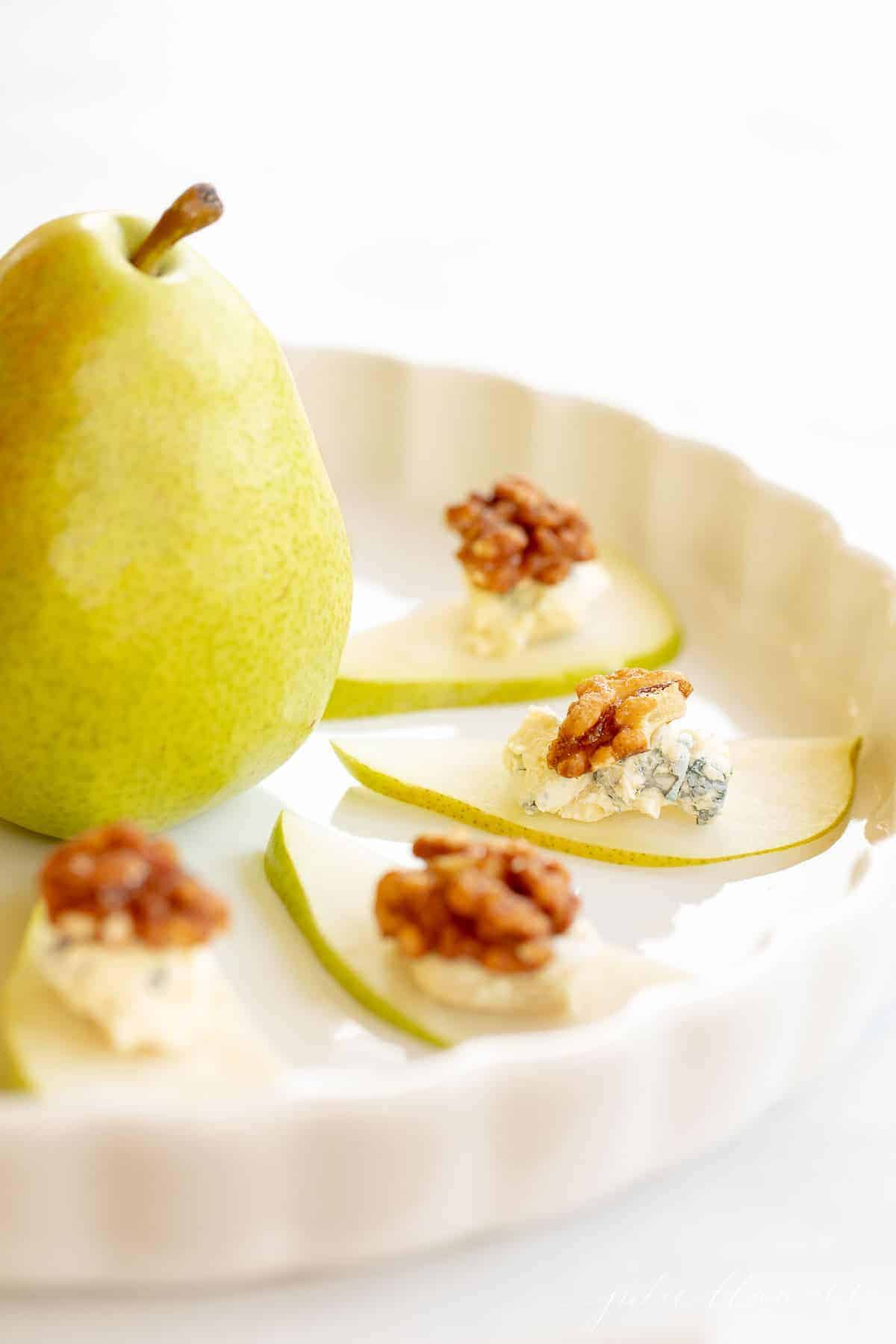 Thin pear slices topped with blue cheese and candied walnuts on a white platter with a pear in the middle.