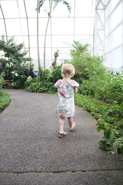 A little girl walking in a garden