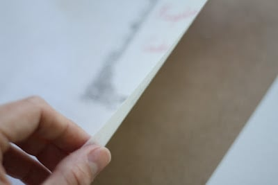 A piece of paper, hand pulling back fabric to separate it.