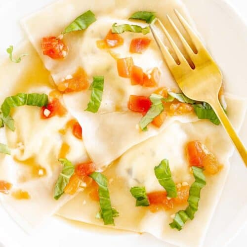 A white plate with goat cheese ravioli in a light tomato sauce, gold fork to the side.