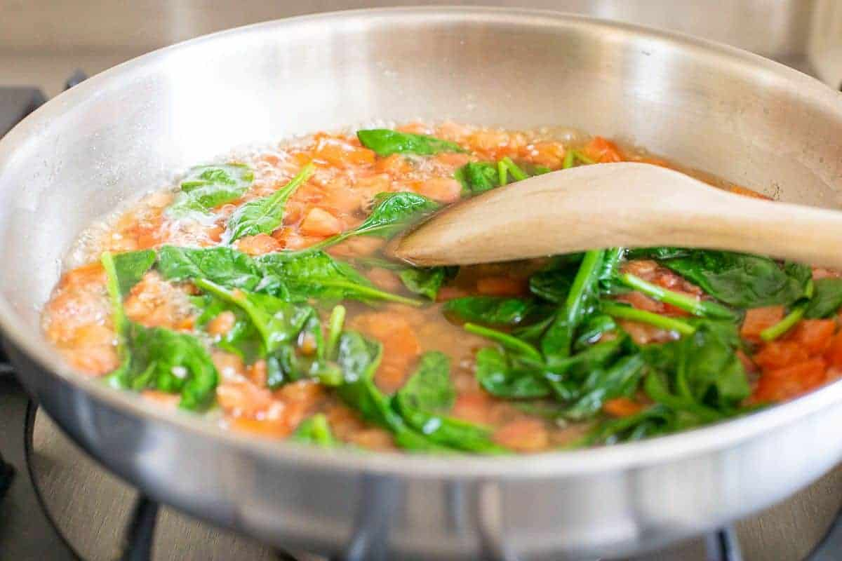 Spinach leaves cooking in a red sauce in a silver pan on a stove.