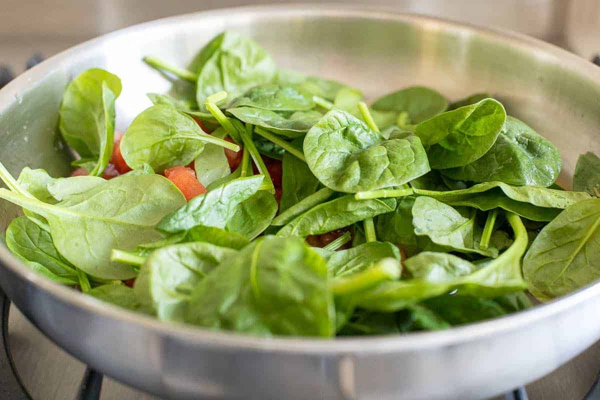 Spinach leaves cooking in a silver pan on a stove.