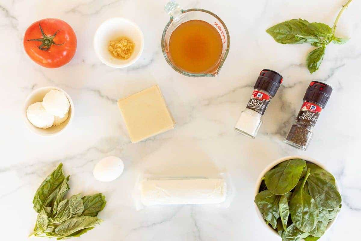A marble surface with ingredients for a goat cheese ravioli recipe laid out.