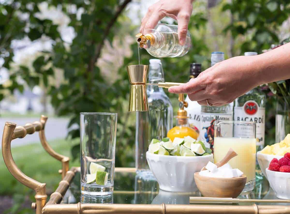 A mojito bar set up on a gold and glass bar cart, a hand reaching over to pour simple syrup in a glass.