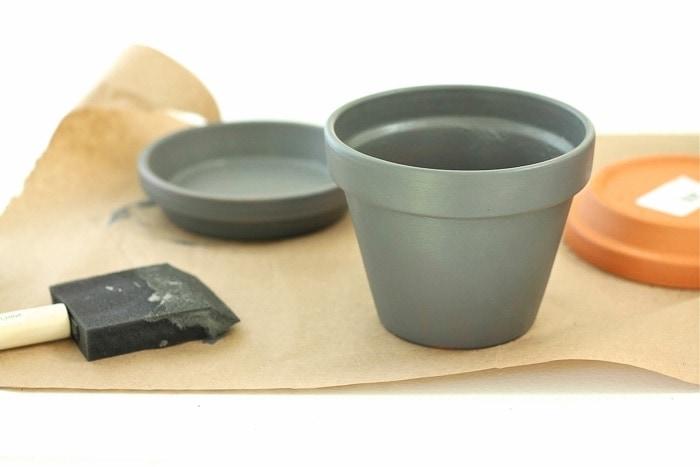 grey pot and saucer next to paint brush