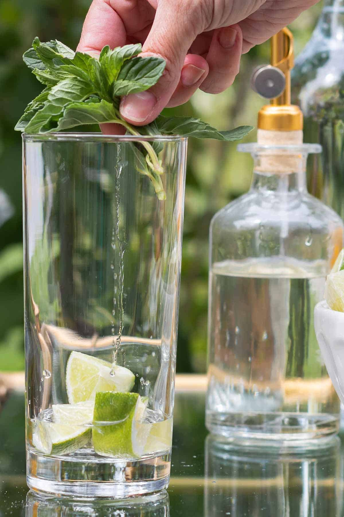 A mojito bar set up on a gold and glass bar cart, a hand reaching over to place fresh mint in a glass.