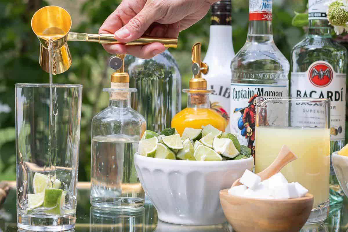 A mojito bar set up on a gold and glass bar cart, a hand reaching over to pour rum in a glass.