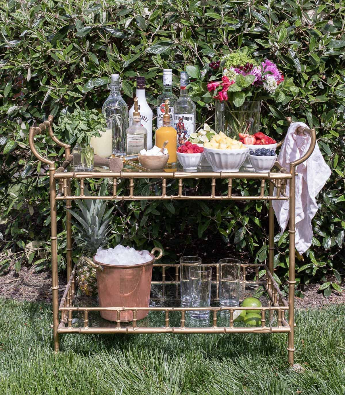A glass and brass bar cart set up with a mojito bar outdoors.