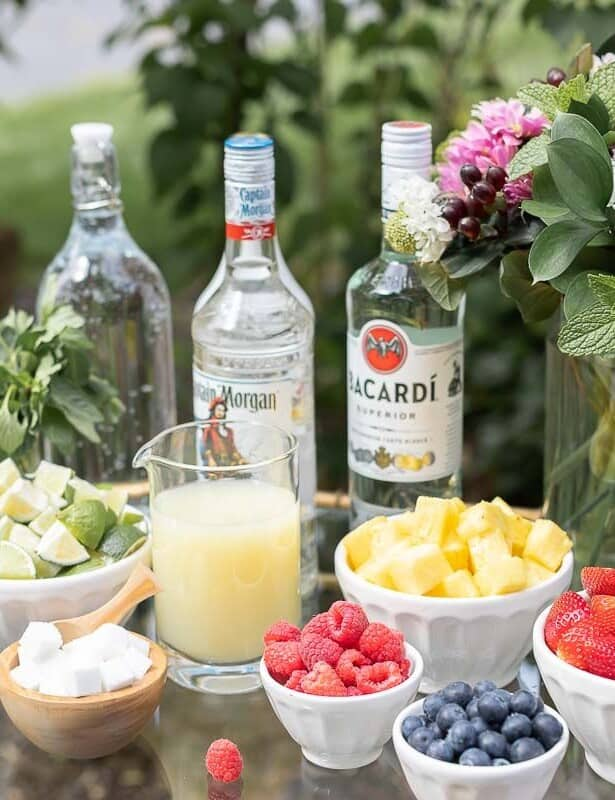 A glass and brass bar cart set up with a mojito bar outdoors, various fruits and limes in bowls beside alcohol bottles.