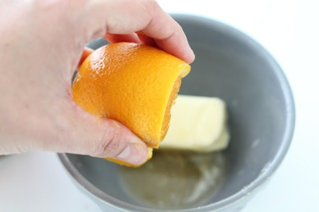 squeezing orange over butter in a bowl