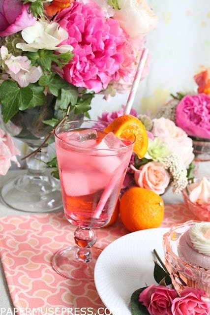 A pink drink with various pink, orange, and purple flowers behind it.