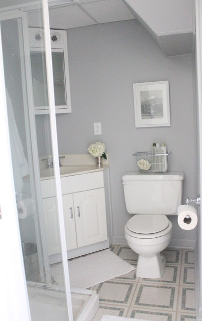 A bathroom with white cabinets and appliances, and gray walls.