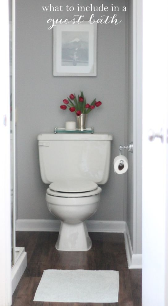 A white toilet with a vase of red flowers on top.