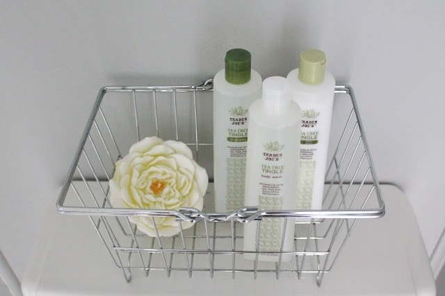 A basket with shampoo, conditioner, body wash, and other shower supplies.