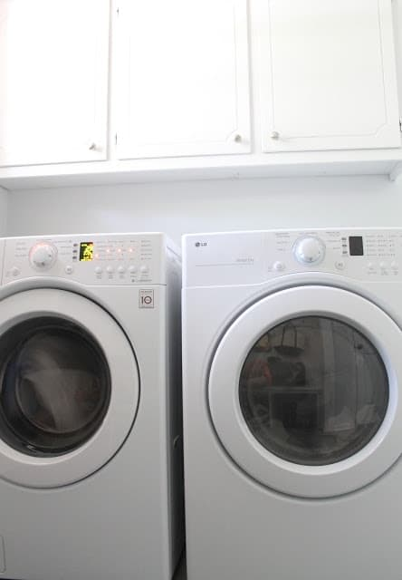 A washer and dryer in a mudroom laundry room with white cabinets.