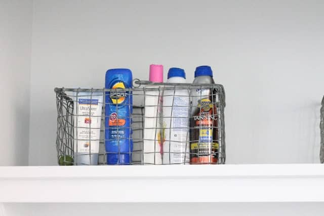 A basket full of sunscreen on the shelf of a mudroom laundry room combination space.