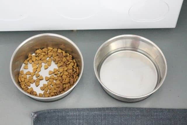 silver dog food and water bowls in a mudroom laundry room space.