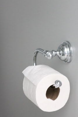 A silver toilet paper holder with toilet paper on it.