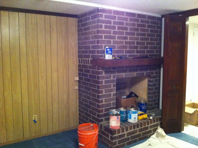A wooden wall with a brick fireplace