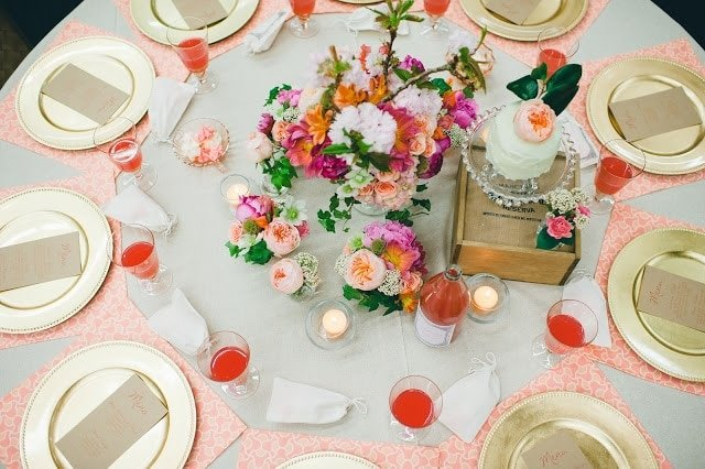 A set table with gold plates, pink, orange, green, and purple flowers with a raspberry cocktail to the side.