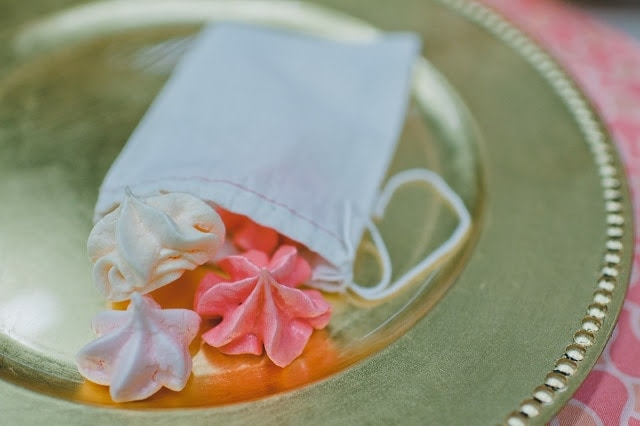 A small white pouch with meringue cookies coming out of it on a gold plate