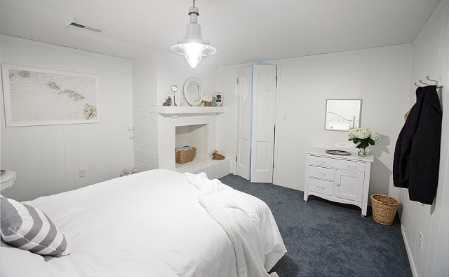 A white bedroom with blue carpet and various knick knacks around on shelves.