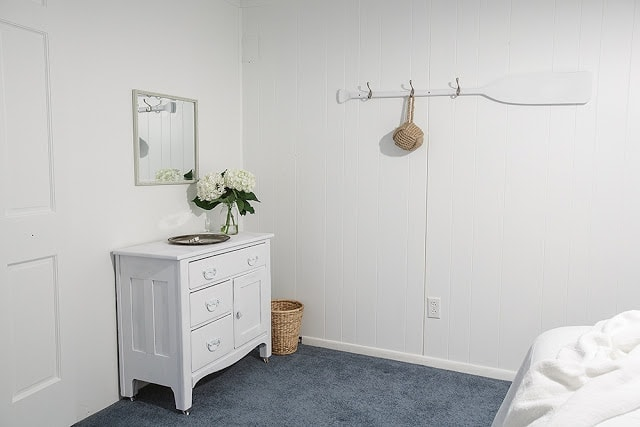A bedroom with a small dresser