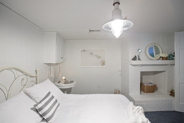A white bedroom with various things on walls and shelves