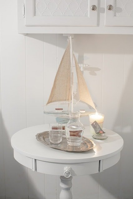 A close up of a side table with a candle, small boat figurine, and water glass.
