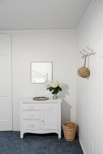 A bedroom with a small dresser and a mirror