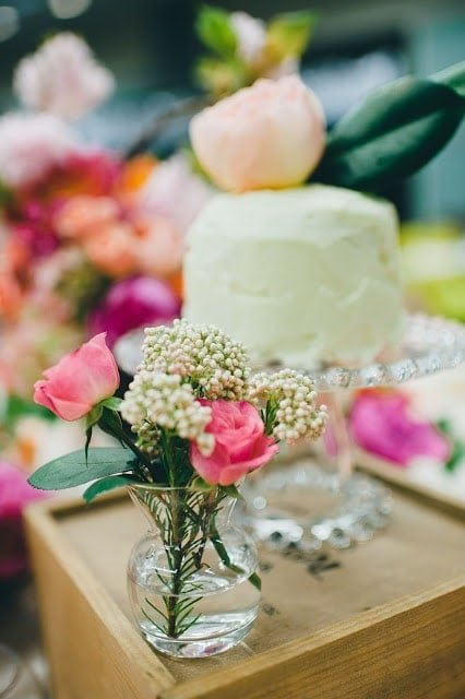 A close up of flowers with a cake in the background