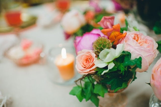 A close up of a pink, orange, green, and purple flowers with a candle to the side
