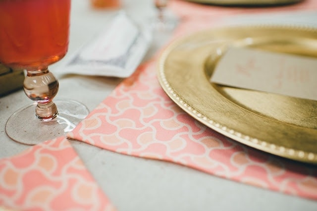 A close up of a gold plate with a coral place mat underneath