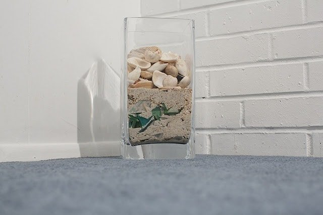 Glass full of sand and shells