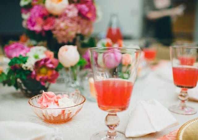 A close up of a pink, orange, green, and purple flowers with a raspberry cocktail to the side.