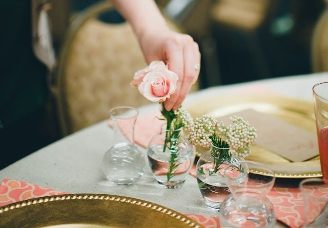 A woman sitting putting pink roses in small, glass vases