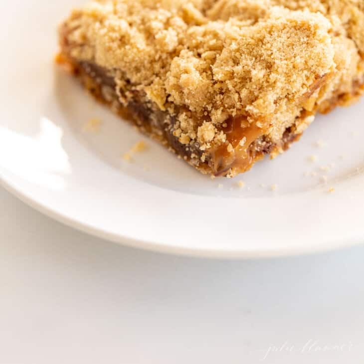 oatmeal cookie bar on white place with caramel oozing out