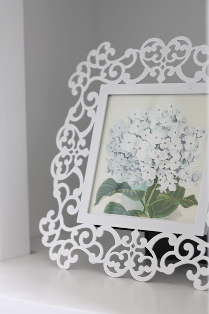 A white picture frame with a picture of a white flower inside.
