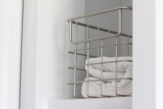 A metal basket with a white towel inside.